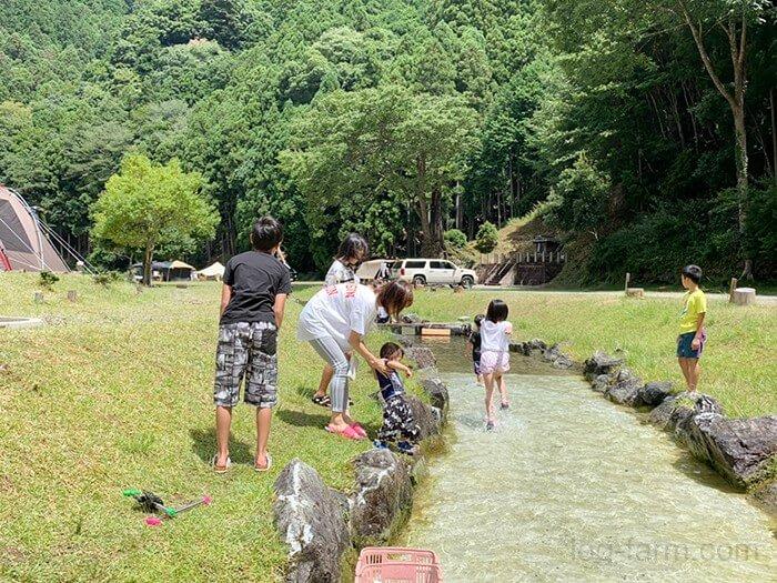 人工の川で遊ぶ小さい子供たち