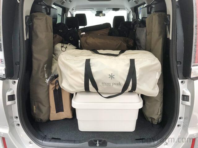 車のトランクにキャンプ道具を積み込み