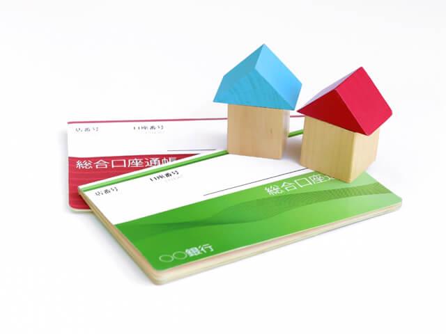 銀行通帳と家の木工細工